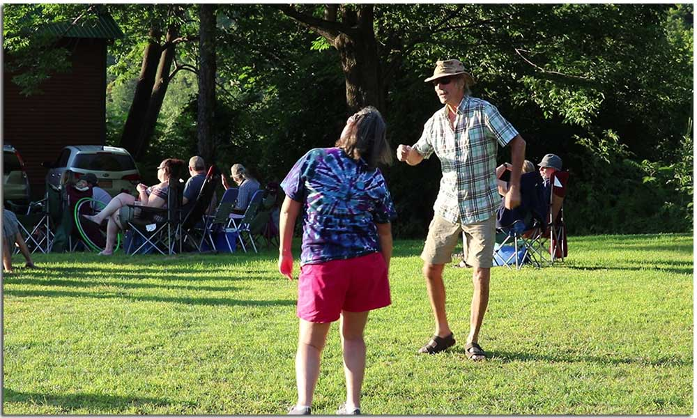 Couple dancing during performance at Music by the River event