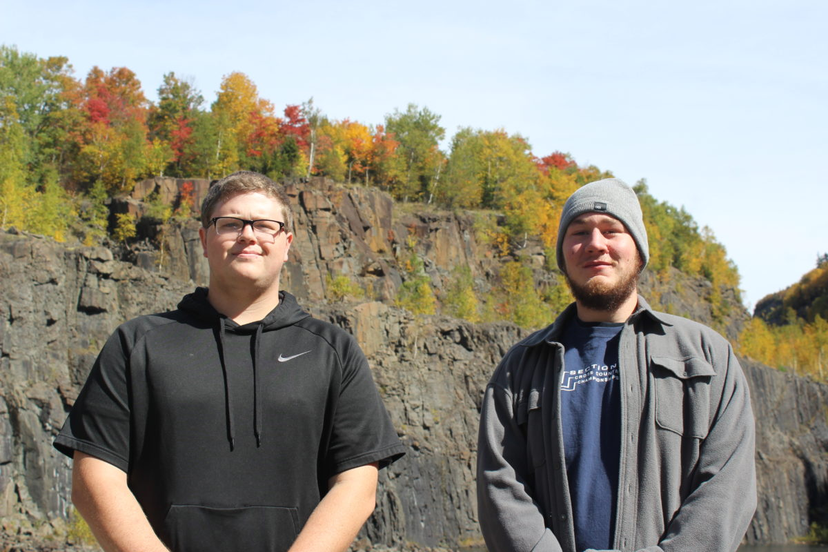 Iron is seen in the rust-colored cliffs behind tour guides Caleb Buck, left, and Dylan Moore, right.