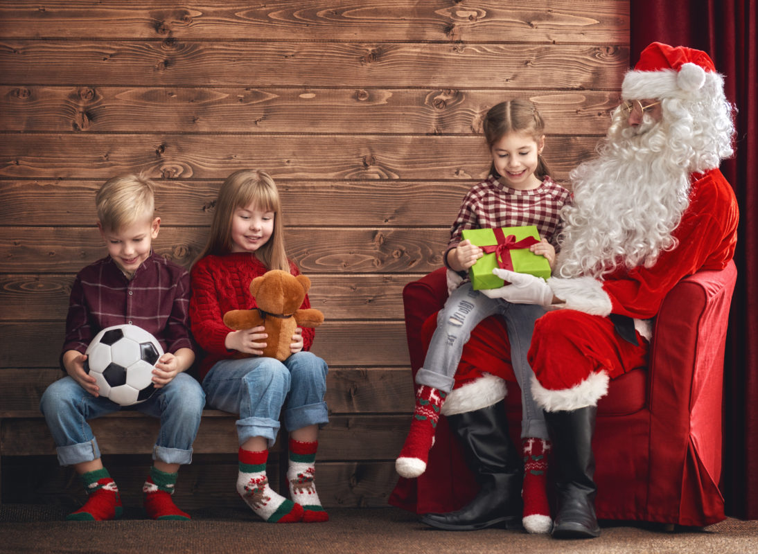 Group of three kids and Santa Claus on wooden background. Kids have presents.