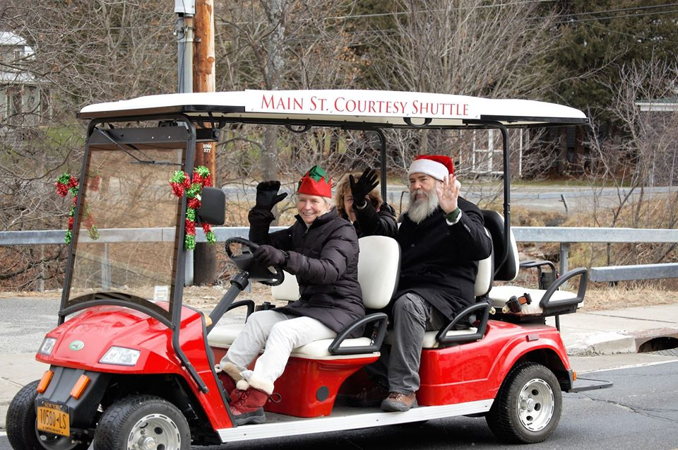People waving from a golf cart in a Christmas parade