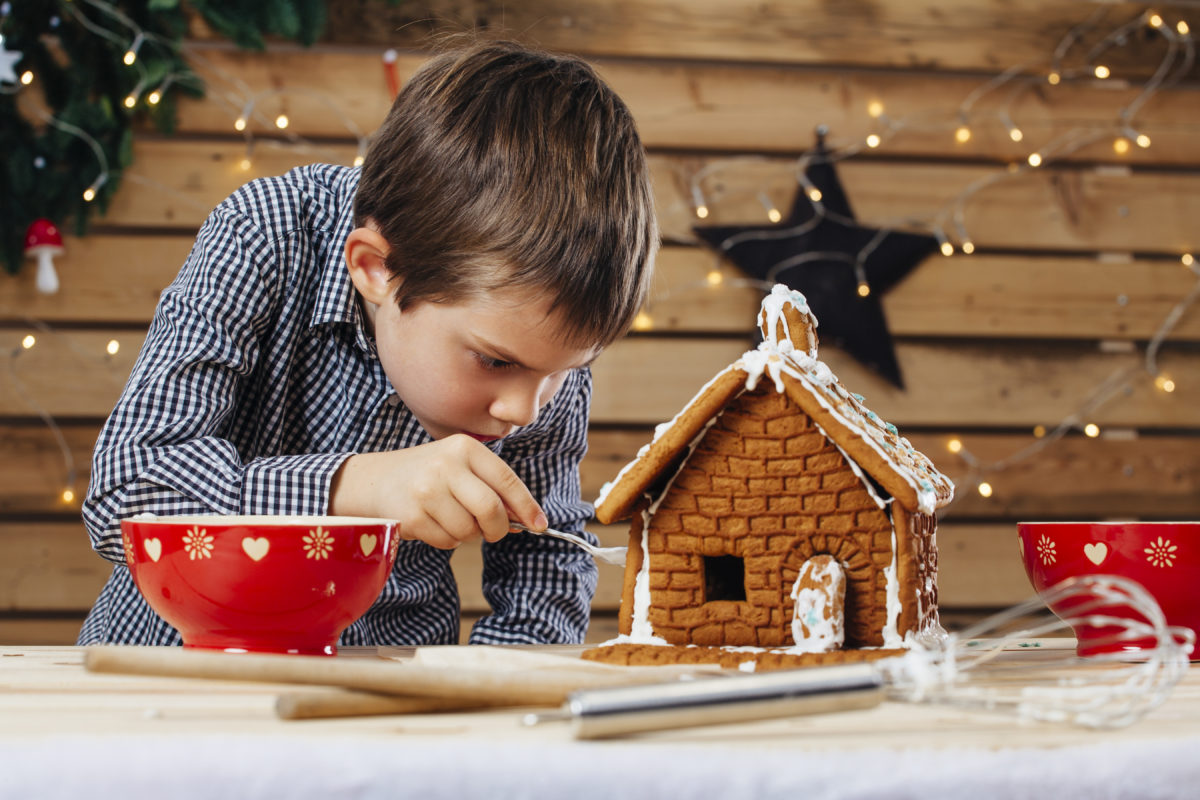 Photo of a young boy decorating a gingerbread house at home just before Christmas.
